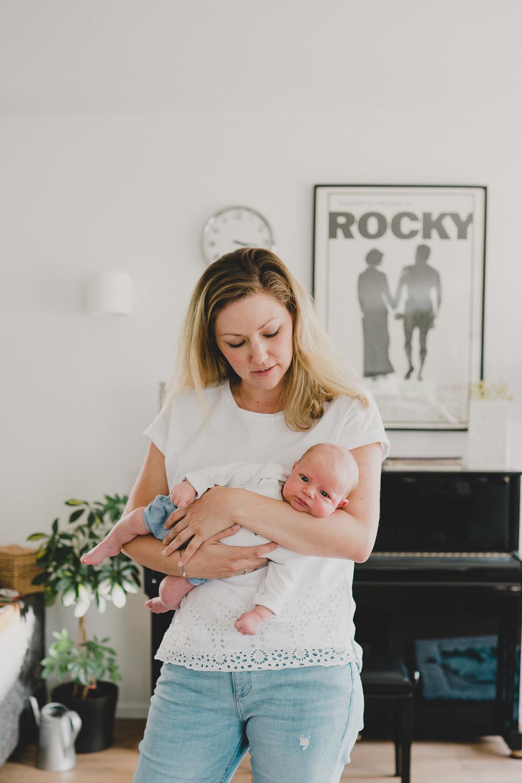 baby bei mama auf dem arm im Wohnzimmer