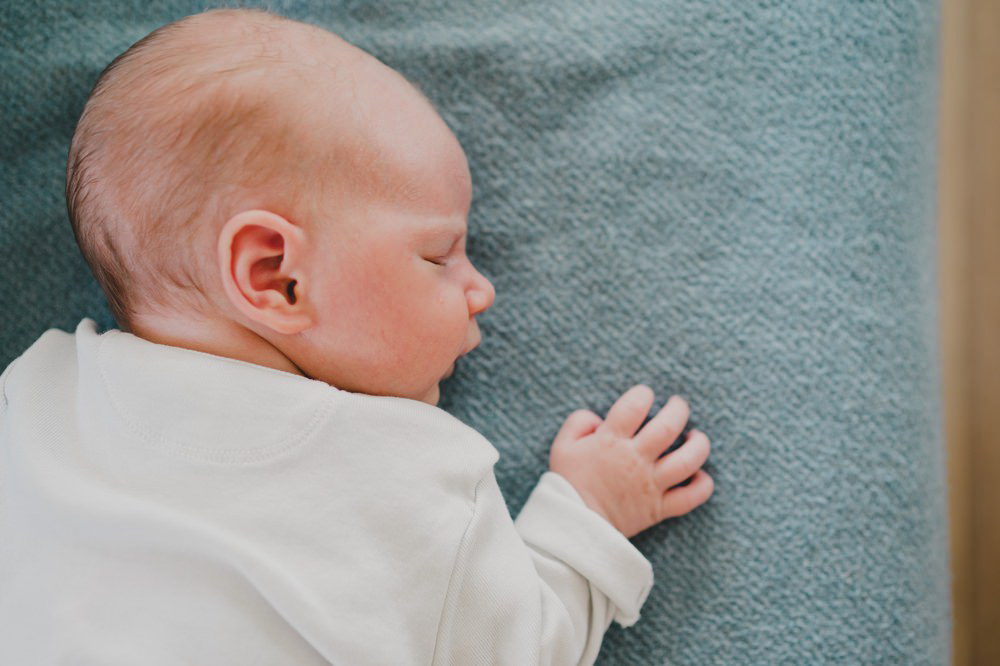 Baby liegt seitlich auf decke und schläft