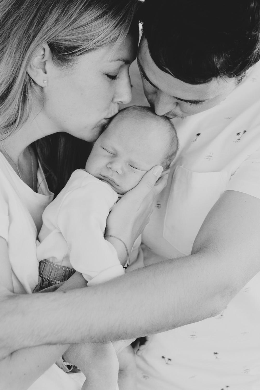mama und Papa küssen Baby in schwarzweiß