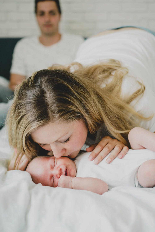 mama küsst liegendes baby