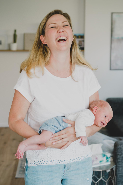 mama lacht und hat baby im arm