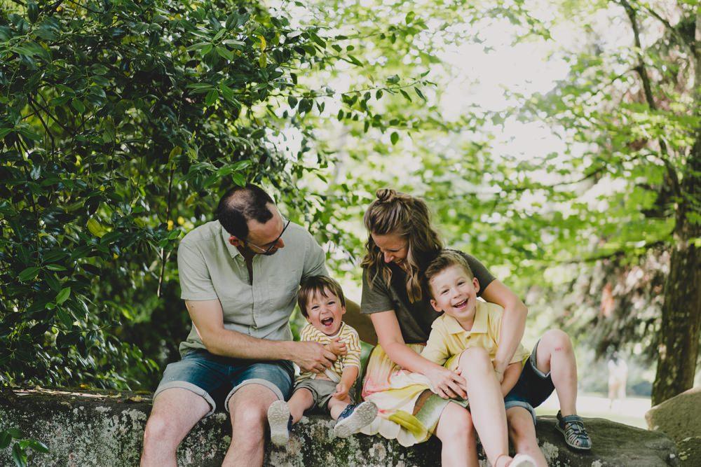 Familie sitzt auf steinen und lacht