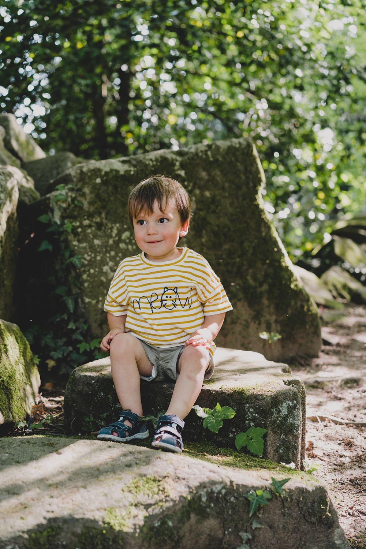 kleiner junge+sitzt auf stein + lacht