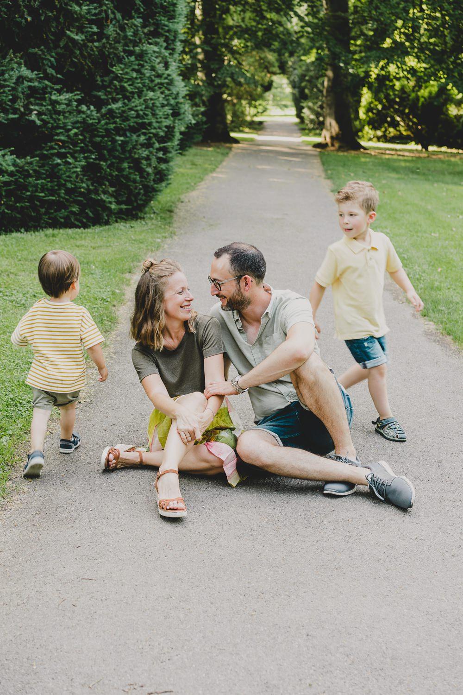 Mama und Papa schauen verliebt+ Kinder laufen um sie herum
